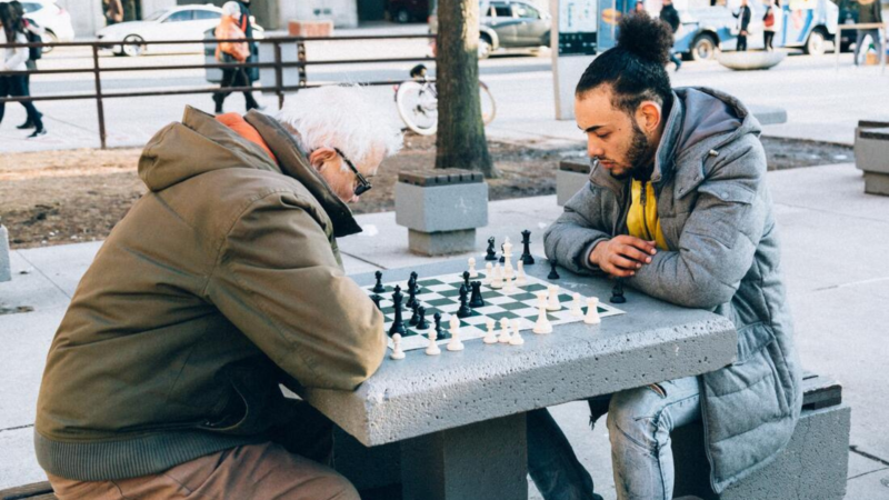 An older man and a younger Latino man play chess in a park.