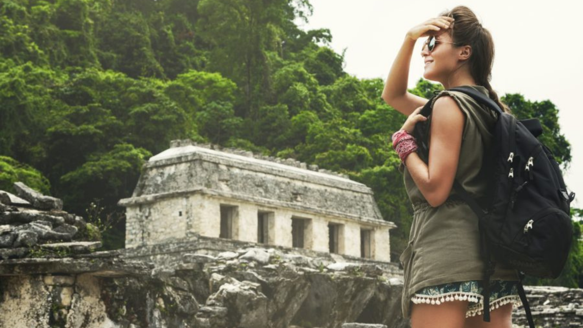 A female tour guide overlooks an ancient temple