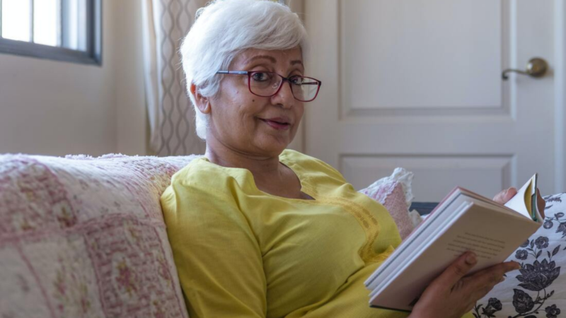 An older woman with white hair sits on a couch studying