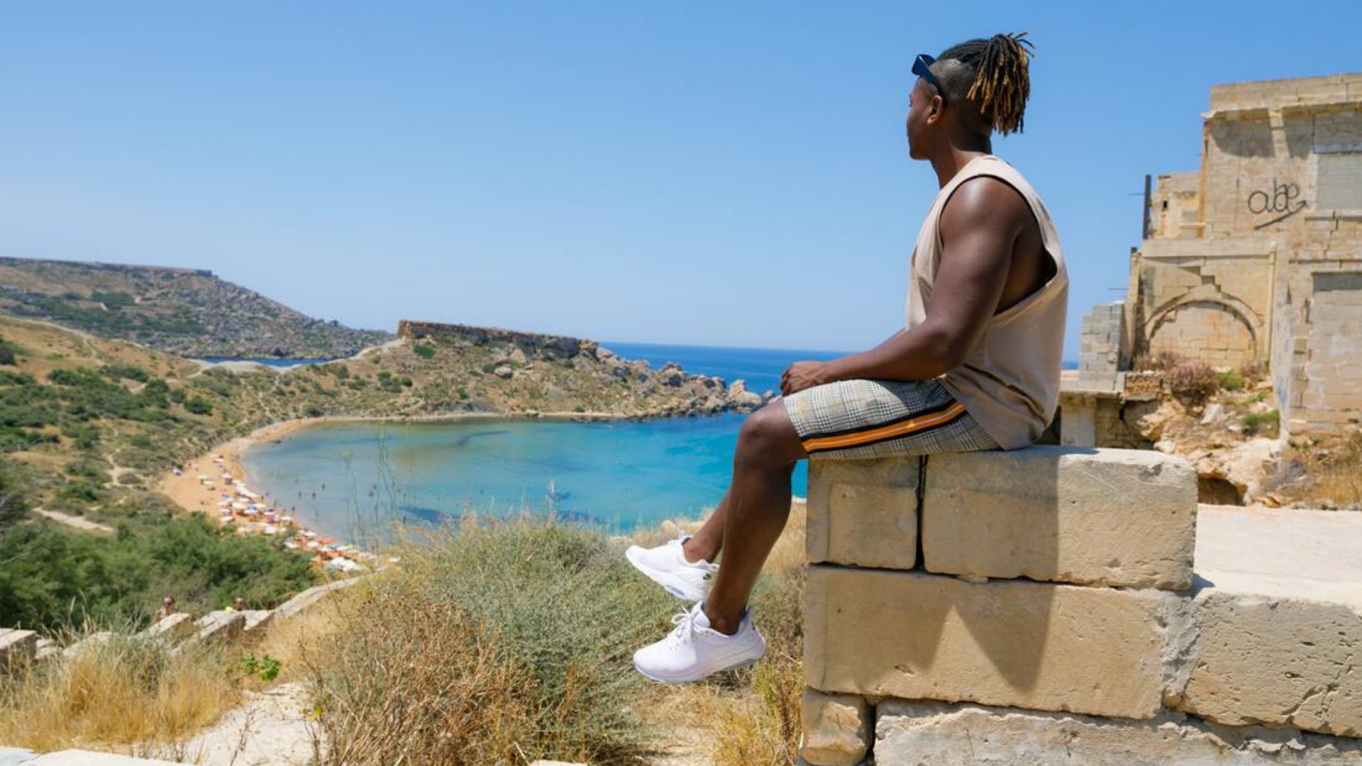 A young black tour guide sits on a stone wall overlooking the sea