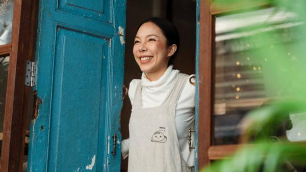 An Asian shopkeeper opens the door