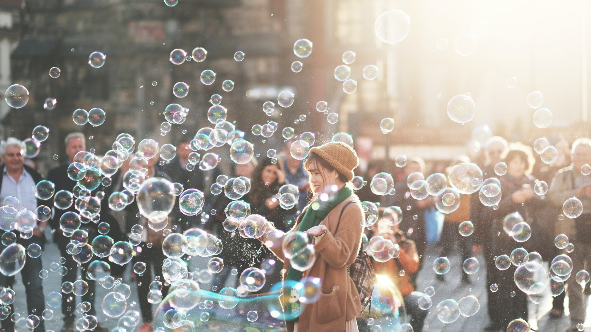 A young Asian woman smiles in a cloud of bubbles