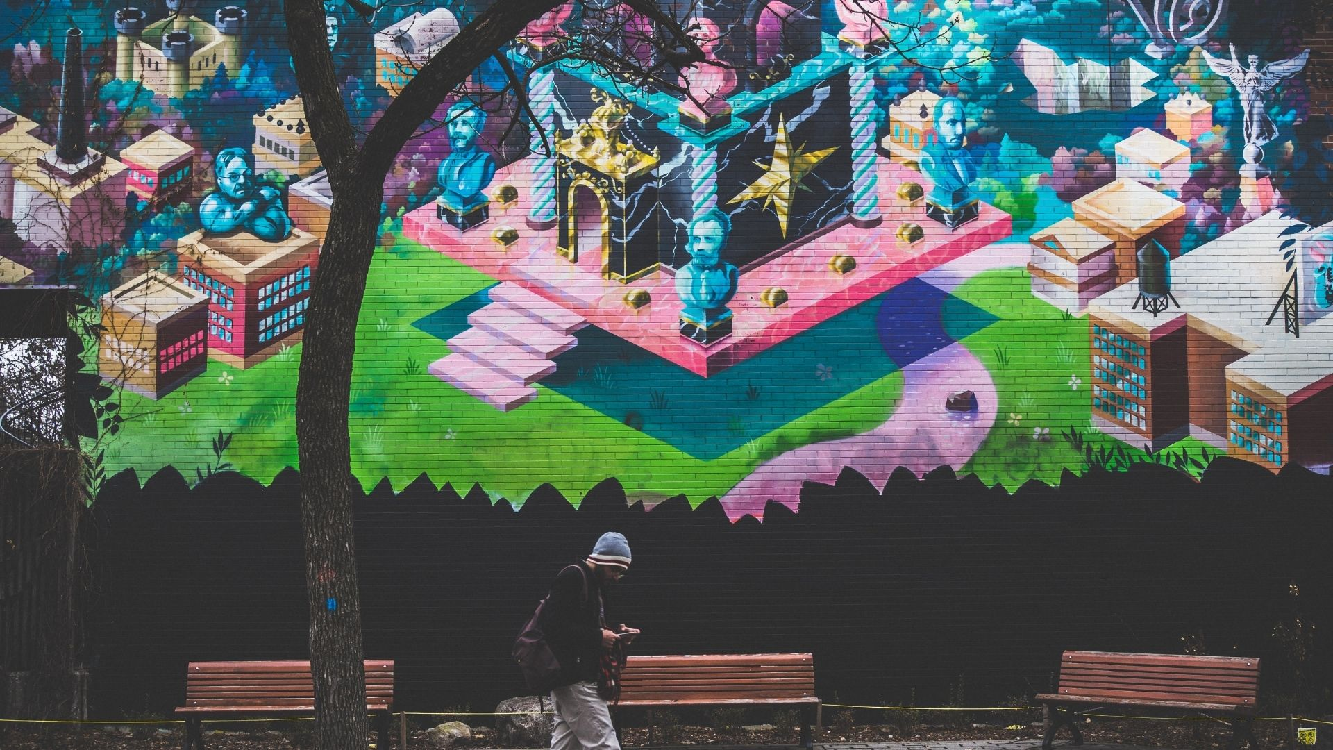 A lone tour guest is on their phone underneath a large street mural.